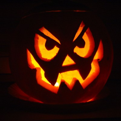 photo of an illuminated Jack O'Lantern with a michievious face carved on it